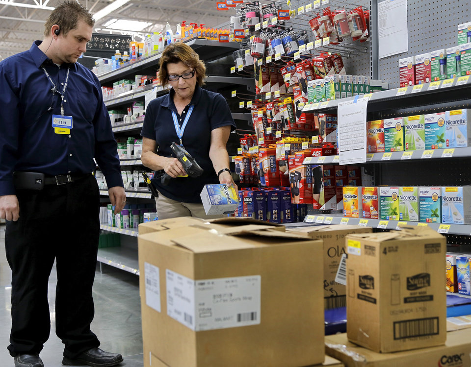 Photo -  Karen Nichols, a merchandise supervisor, scans merchandise while store co-manager Gene Simmons stops to check on progress as employees and managers prepare for the opening of Choctaw's first Walmart in July. Photo by Jim Beckel, The Oklahoman   Jim Beckel -