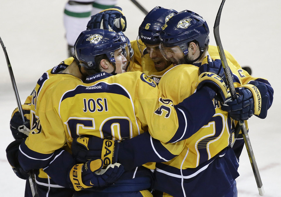Photo - Nashville Predators defenseman Roman Josi (59), of Switzerland, celebrates with Shea Weber (6) and Paul Gaustad (28) after Josi scored against the Dallas Stars in the second period of an NHL hockey game Monday, Jan. 20, 2014, in Nashville, Tenn. (AP Photo/Mark Humphrey)