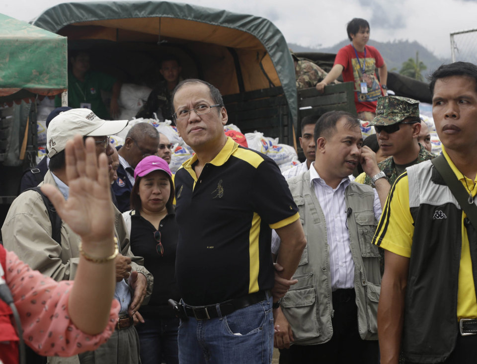 Philippine President Benigno Aquino III talks to local government officials prior to distributing relief goods to victims of Typhoon Bopha at New Bataan township, Compostela Valley in southern Philippines, Friday Dec. 7, 2012. Rescuers were digging through mud and debris Friday to retrieve more bodies strewn across the farming valley by the powerful typhoon. (AP Photo/Bullit Marquez)