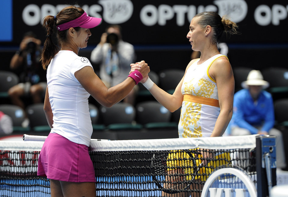 Photo - Li Na of China, left, shakes hands with  Flavia Pennetta of Italy at the net, after Li won their quarterfinal at the Australian Open tennis championship in Melbourne, Australia, Tuesday, Jan. 21, 2014.(AP Photo/Andrew Brownbill)