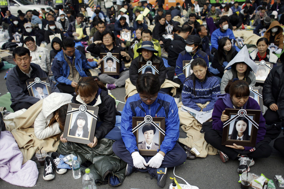 Photo - Family members holding the portraits of the victims of the sunken ferry Sewol, sit on a street near the presidential Blue House in Seoul, South Korea, Friday, May 9, 2014. Family members marched to the presidential Blue House in Seoul early Friday calling for a meeting with President Park Geun-hye but ended up sitting on streets near the presidential palace after police officers blocked them. Park's office said a senior presidential official plans to meet them later Friday. (AP Photo/Lee Jin-man)