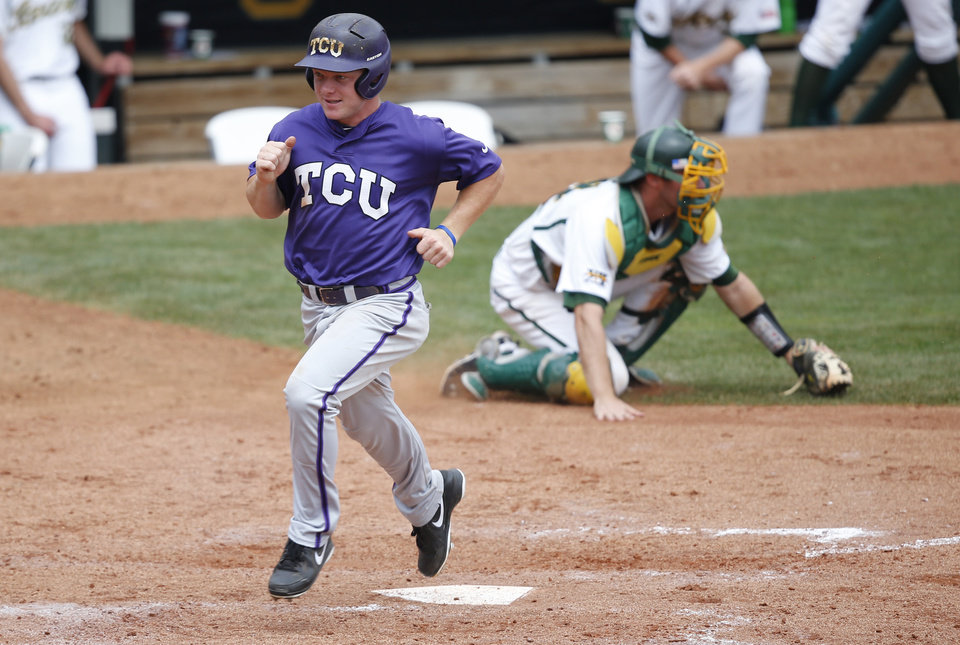 Photo - TCU's Boomer White crosses the plate and scores in front of Baylor catcher Nate Goodwin, right, in the seventh inning of a game in the Big 12 conference NCAA college baseball tournament in Oklahoma City, Saturday, May 24, 2014. TCU won 4-1 and advances to the championship game on Sunday. (AP Photo/Sue Ogrocki)
