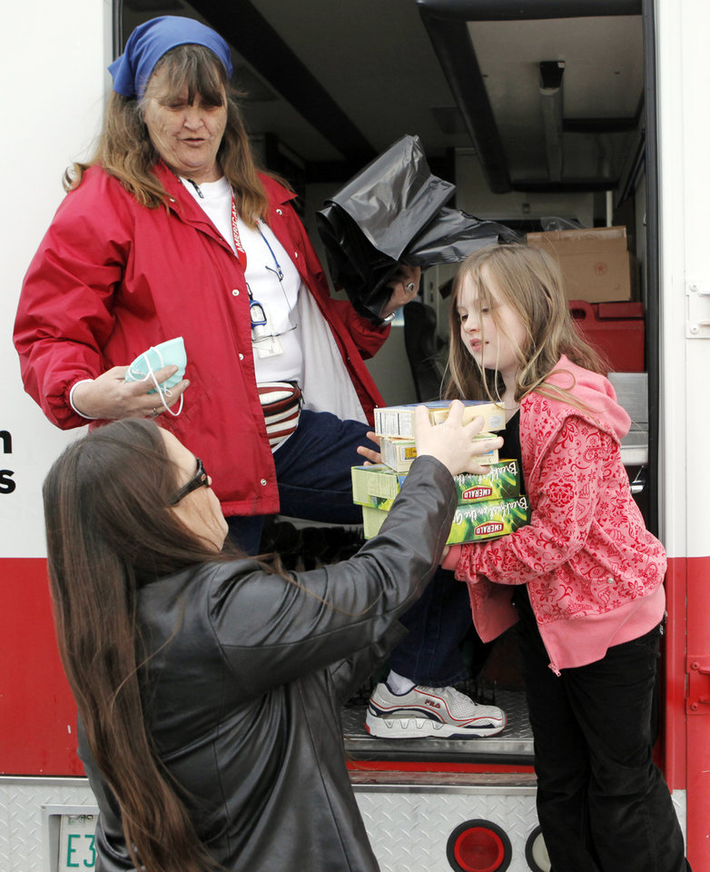 Photo - FIRES / RELIEF / ASSISTANCE / AID: Red Cross volunteer Liz McKeel, upper left, gives relief items to Christina Myers, bottom left, and her daughter, Braylin Stilwell-Love, 8, right, at the Red Cross field office at Douglas Boulevard United Methodist Church, 208 S Douglas Boulevard, in Midwest City, Okla., Monday, April 13, 2009. Christina Myers lost the home she lived in with her two children and husband at 14221 E Reno Avenue in Choctaw, Okla., in the wildfires on Thursday, April 9, 2009. Photo by Nate Billings, The Oklahoman ORG XMIT: KOD