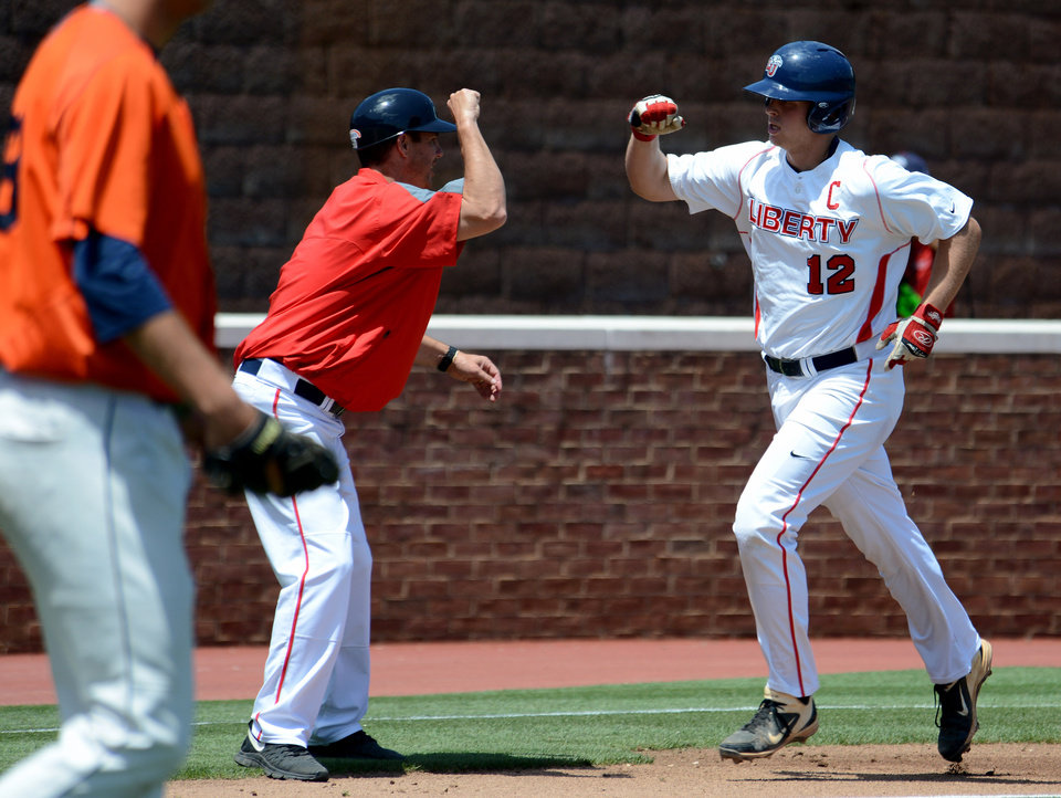 Photo - Liberty's Alex Close is congratulated after hitting a solo home run during the first inning of an NCAA college baseball regional tournament game against Bucknell in Charlottesville, Va., Saturday, May 31, 2014. (AP Photo/Pat Jarrett)