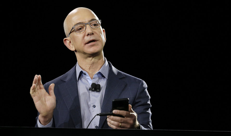 Photo - Amazon CEO Jeff Bezos demonstrates the new Amazon Fire Phone during a launch event Wednesday, June 18, 2014, in Seattle. (AP Photo/Ted S. Warren)