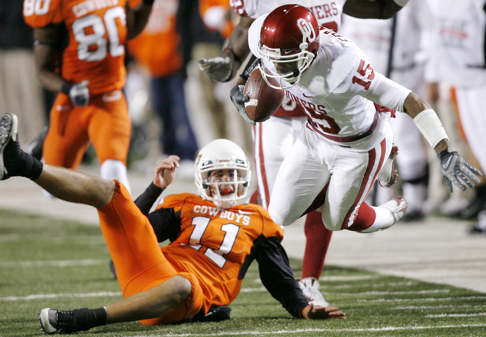 Oklahoma's Dominique Franks (15) is tripped up by Oklahoma State's Zac Robinson (11) after Franks intercepted Robinson's pass during the first half of the college football game between the University of Oklahoma Sooners (OU) and Oklahoma State University Cowboys (OSU) at Boone Pickens Stadium on Saturday, Nov. 29, 2008, in Stillwater, Okla. STAFF PHOTO BY CHRIS LANDSBERGER