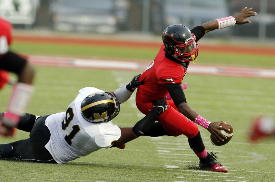 Bomber Brandon Jones brings down Del City quarterback Terry Wilson for a loss as the Eagles play the Midwest City Bombers in high school football on Friday, Sept. 20, 2013 in Del City, Okla.  Photo by Steve Sisney, The Oklahoman
