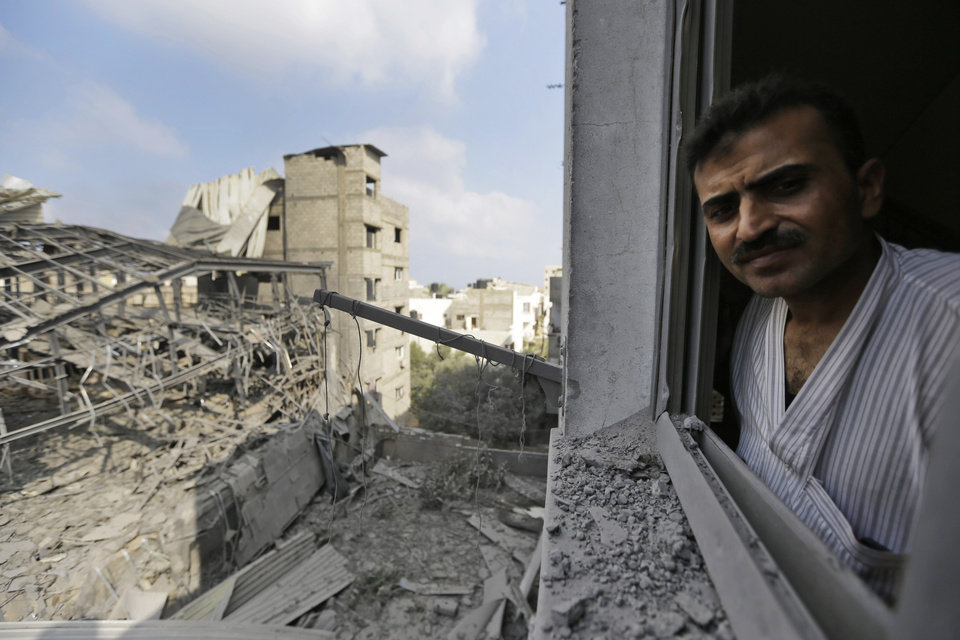 Photo - A Palestinian from a damaged neighboring apartment building inspects the damage of the offices of the Hamas movement's Al-Aqsa satellite TV station, left, in Gaza City, northern Gaza Strip, destroyed by an Israeli strike, Tuesday, July 29, 2014. Early Tuesday, Israel warplanes struck a series of targets in Gaza City, including the top Hamas leader in Gaza, Ismail Haniyeh's house and government offices, while Gaza's border area with Israel was hit by heavy tank shelling. (AP Photo/Lefteris Pitarakis)