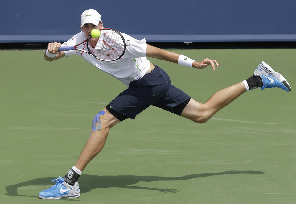 Photo - FILE - In this Aug. 14, 2014, file photo, John Isner returns a serve against Andy Murray, from Great Britain, during a match at the Western & Southern Open tennis tournament in Mason, Ohio. Heading into the U.S. Open, Roger Federer, Rafael Nadal, Novak Djokovic and Andy Murray have won 36 of the past 38 Grand Slam titles, a stretch dating to the 2005 French Open. Nowadays, there seems to be a growing sense _ or hope, maybe _ among the best of the rest on the men's tennis tour that the quartet might be more vulnerable than ever.(AP Photo/Al Behrman, File)