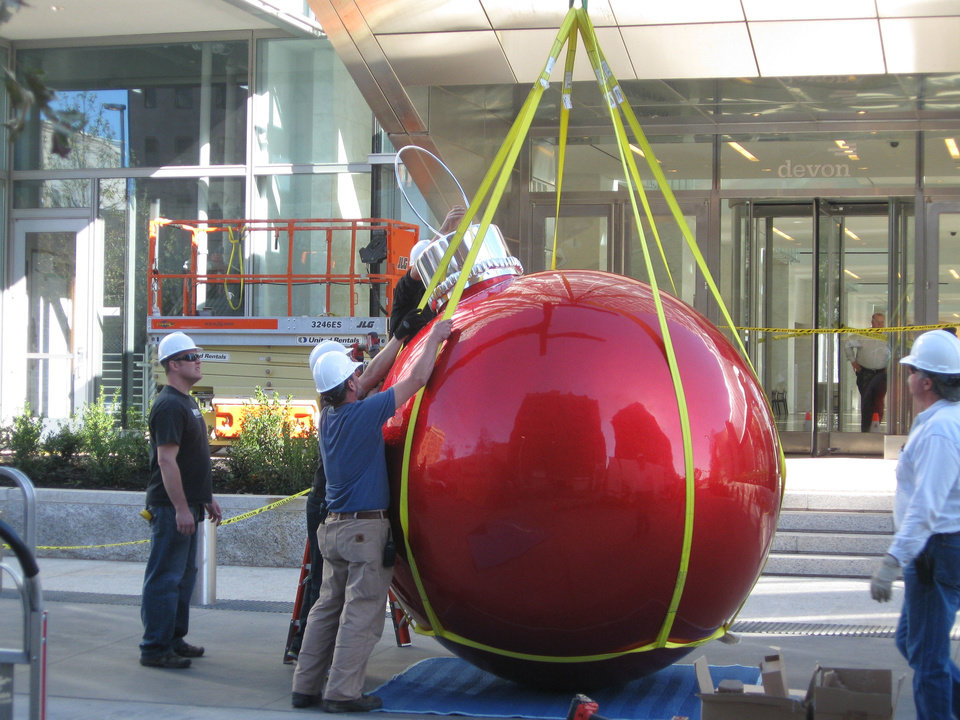 A crew prepares to hang the first Christmas bulb near the west entrance to Devon Energy Center along Hudson Avenue. Photo by Steve Lackmeyer, The Oklahoman
