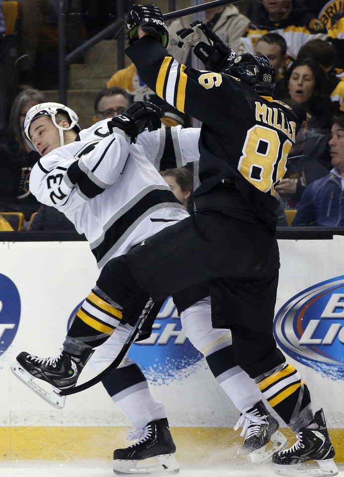 Photo - Los Angeles Kings right wing Dustin Brown (23) is checked into the boards by Boston Bruins defenseman Kevan Miller (86) during the first period of an NHL hockey game in Boston Monday, Jan. 20, 2014. (AP Photo/Elise Amendola)