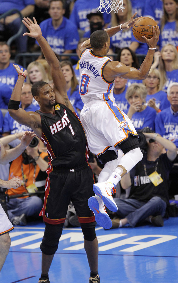 Oklahoma City's Russell Westbrook (0) drives past Miami's Chris Bosh (1) during Game 2 of the NBA Finals between the Oklahoma City Thunder and the Miami Heat at Chesapeake Energy Arena in Oklahoma City, Thursday, June 14, 2012. Photo by Chris Landsberger, The Oklahoman