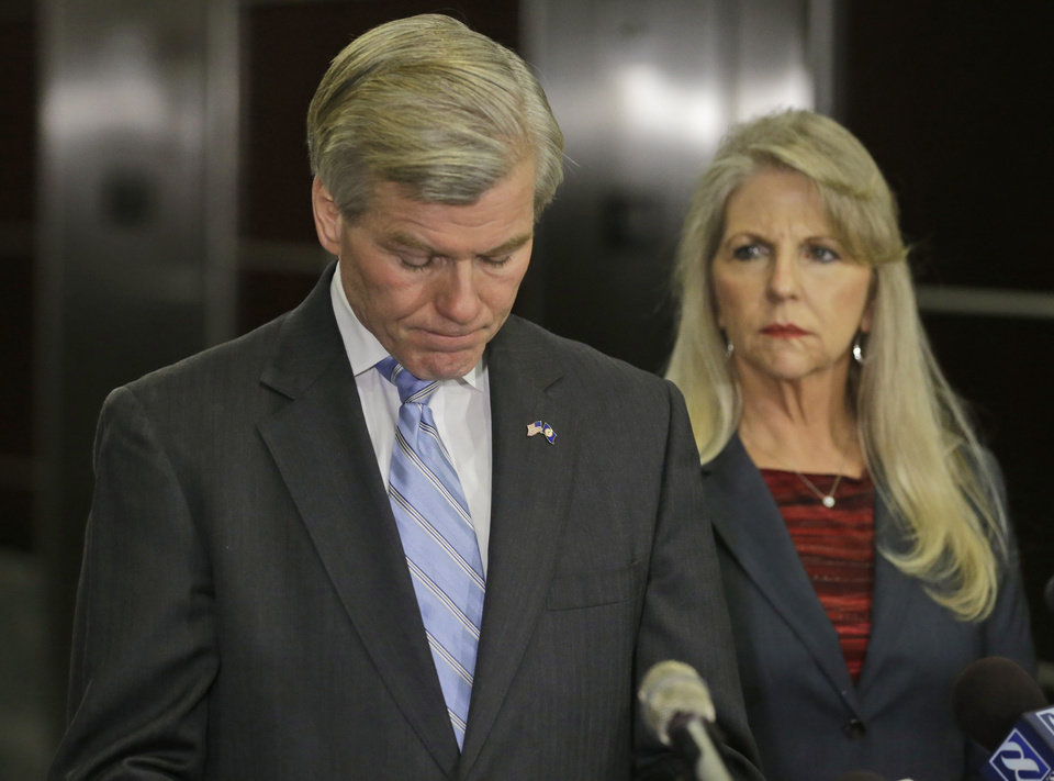 Photo - Former Virginia Governor Bob McDonnell takes a moment while making a statement as his wife, Maureen, right,  looks on during a news conference in Richmond, Va., Tuesday, Jan. 21, 2014.  McDonnell and his wife were indicted Tuesday on corruption charges after a monthslong federal investigation into gifts the Republican received from a political donor.  (AP Photo/Steve Helber)
