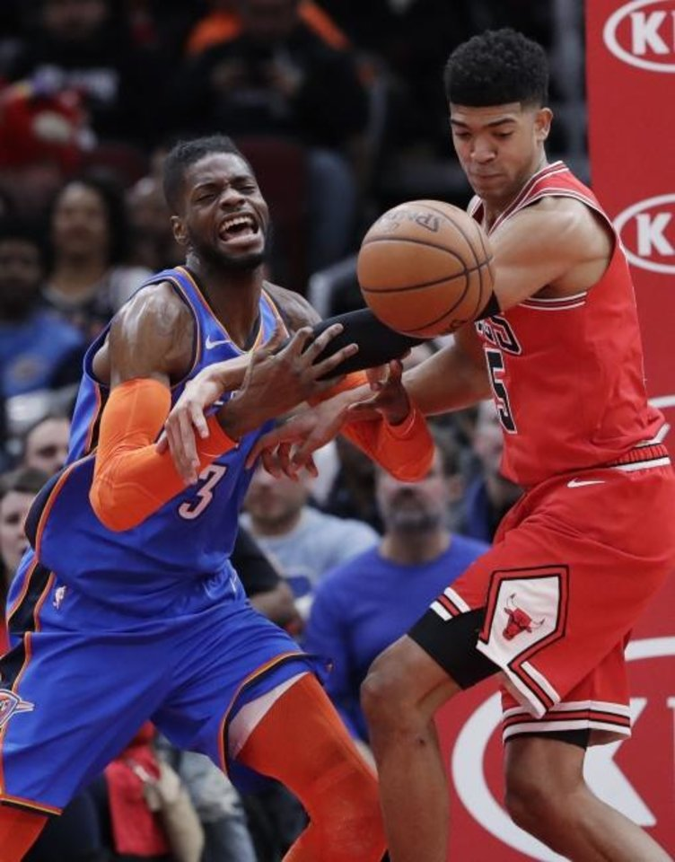 Photo - Oklahoma City Thunder's Nerlens Noel, left, and Chicago Bulls' Chandler Hutchison reach for a loose ball during the second half of an NBA basketball game Friday, Dec. 7, 2018, in Chicago. The Bulls won 114-112. (AP Photo/Nam Y. Huh)