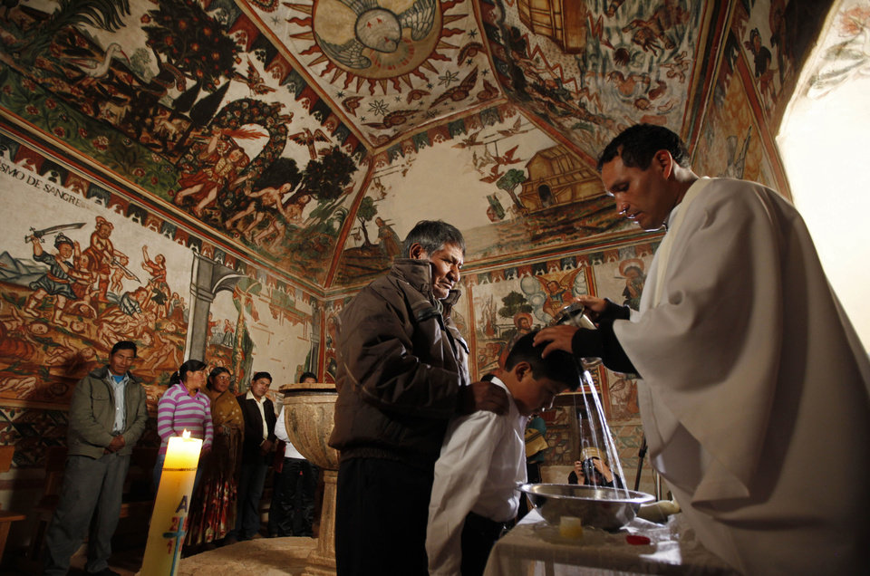 A boy is baptized by Father Gabriel Antequera at the Sistine Chapel of Los Andes in Curahuara de Carangas, Oruro department, 260 km. (160 miles) south from La Paz, Bolivia, Saturday, Dec. 8, 2012. The colonial-era house of worship known in Bolivia as the Sistine Chapel of the Andes was filled with flowers over the weekend for those celebrating two weddings and seven baptisms on the wind swept mountain plateau.(AP Photo/Juan Karita)