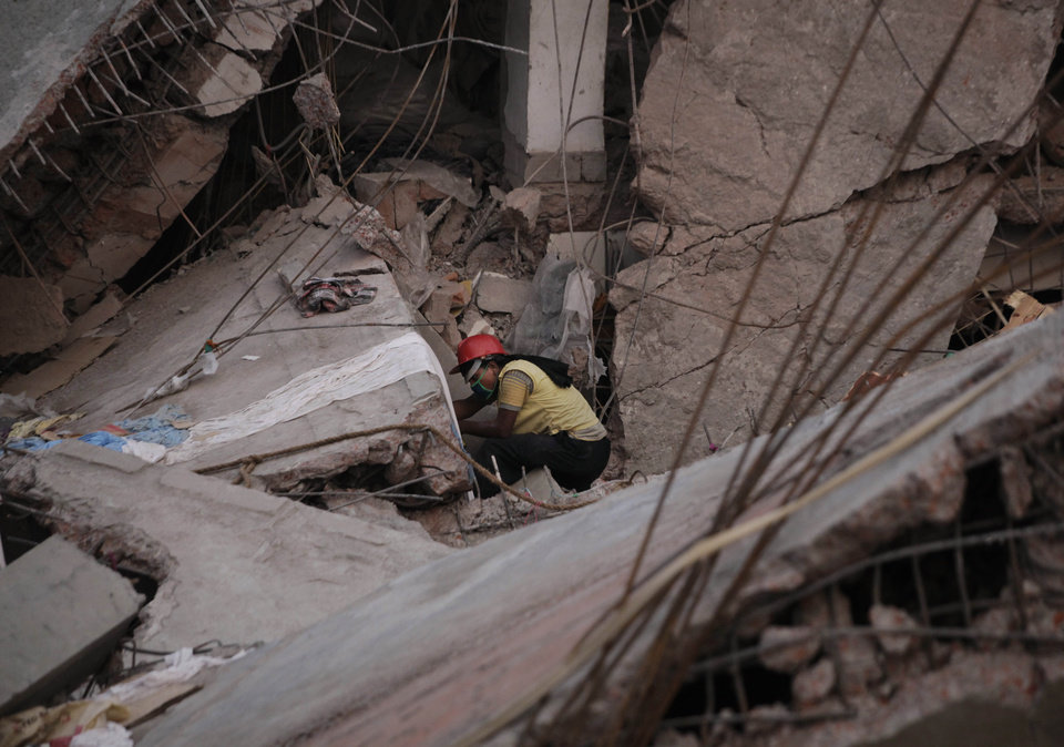 Photo - FILE - In this April 27, 2013 file photo, a Bangladeshi rescue worker searches alone in a building that collapsed Wednesday, April 24, 2013, in Savar, near Dhaka, Bangladesh. The owner of the building, who ignored inspectors who advised to close the structure when cracks appeared in the building a day before the collapse,  sits at the nexus of party politics and the powerful $20 billion garment industry that drives the economy of this deeply impoverished nation. Experts say this intersection of politics and business, combined with a minimum wage of $9.50 a week that has made Bangladesh the go-to nation for many of the world's largest clothing brands, has created a predictable danger for factory workers. Government officials, labor activists, manufacturers and retailers all called for improved safety standards after a November fire in the same suburb, when locked emergency exits trapped hundreds of garment workers inside amid spreading flames and 112 people died. But almost nothing has changed.  (AP Photo/Kevin Frayer, File)