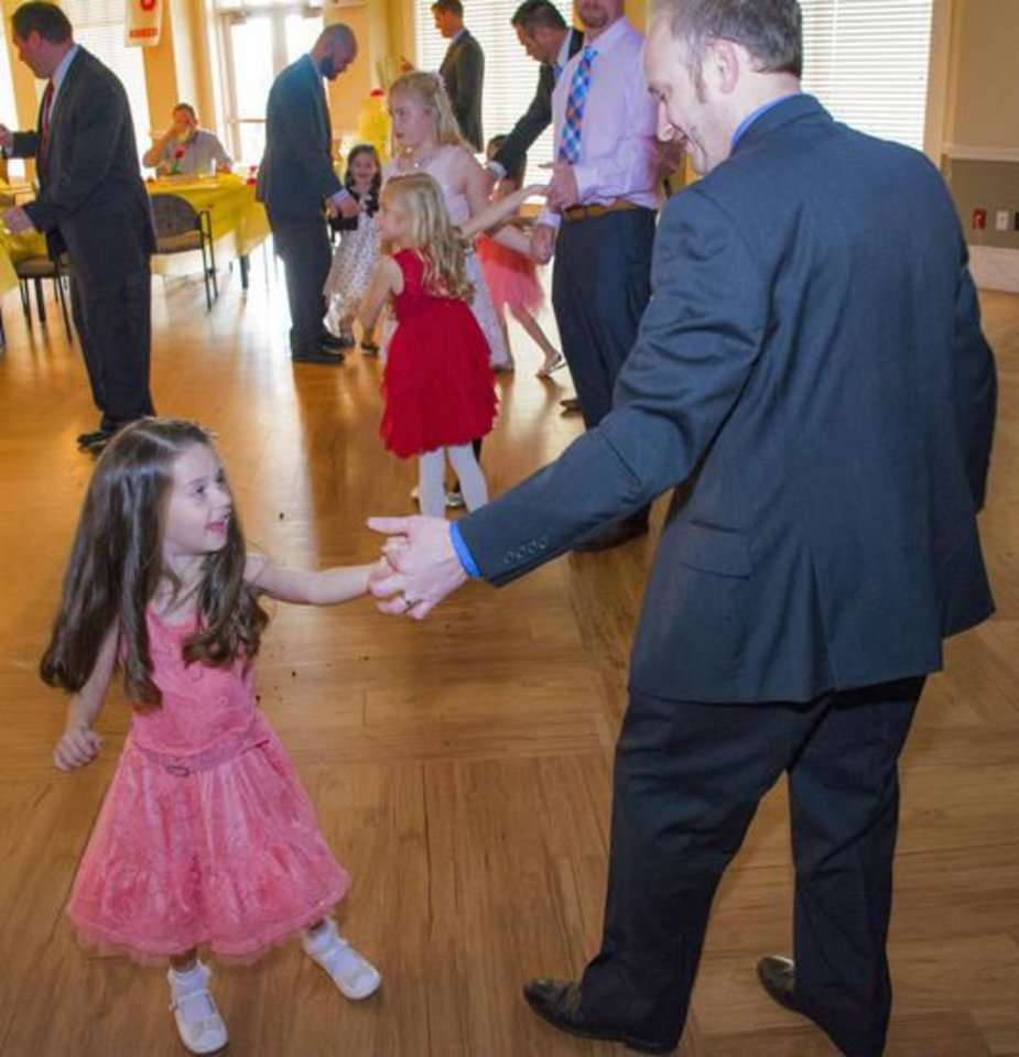 Photo -  Jaylee Ernst, 5, Edmond, dances with her father, Travis Ernst, during the Daddy-Daughter Dance in Edmond. [PHOTO BY ERIECH TAPIA, FOR THE OKLAHOMAN]
