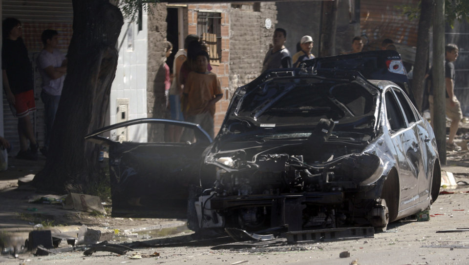 A damaged car is seen on the street after looters tried to enter a supermarket on the outskirts of Buenos Aires, Argentina, Friday, Dec. 21, 2012. Two people were killed in Argentina as looters ransacked supermarkets in several cities, officials said Friday. Santa Fe Province Security Minister Raul Lamberto said the incidents were not triggered by social protests but were simple acts of vandalism. (AP Photo/Natacha Pisarenko)