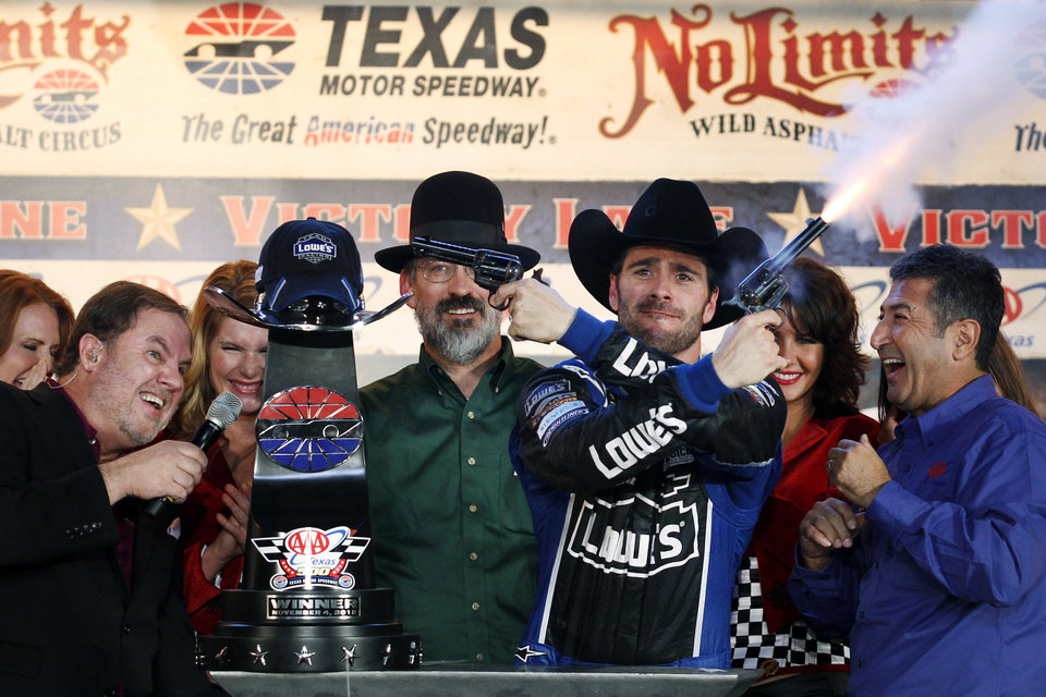 Track President Eddie Gossage, left, ducks as Jimmie Johnson fires blanks out of a revolver while celebrating in victory lane following his win in the NASCAR Sprint Cup Series auto race at Texas Motor Speedway, Sunday, Nov. 4, 2012, in Fort Worth, Texas. (AP Photo/Tim Sharp) ORG XMIT: TMS225