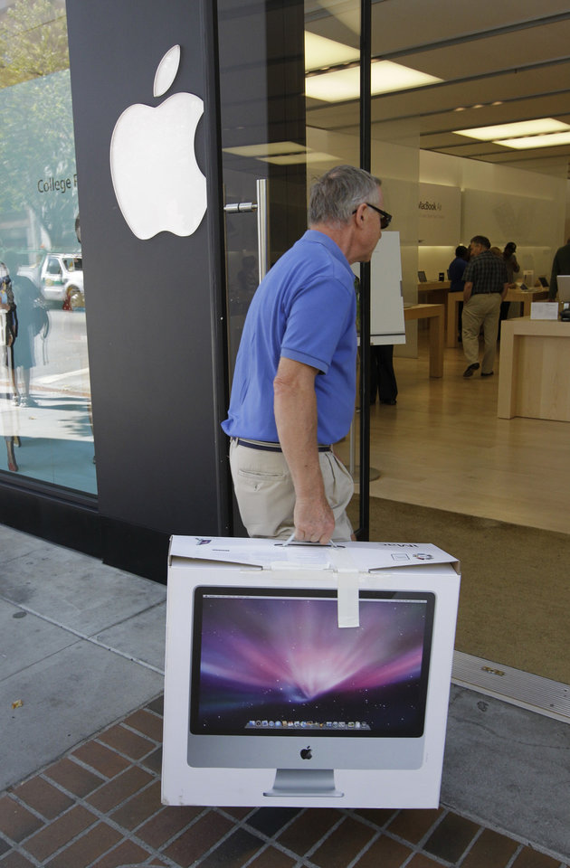 In this Thursday, July 19, 2012, photo, An Apple customer returns an Apple 21.5-inch iMac computer to an Apple store in Palo Alto, Calif. Apple Inc. reports quarterly financial results after the market closes on Tuesday, July 24. (AP Photo/Paul Sakuma)