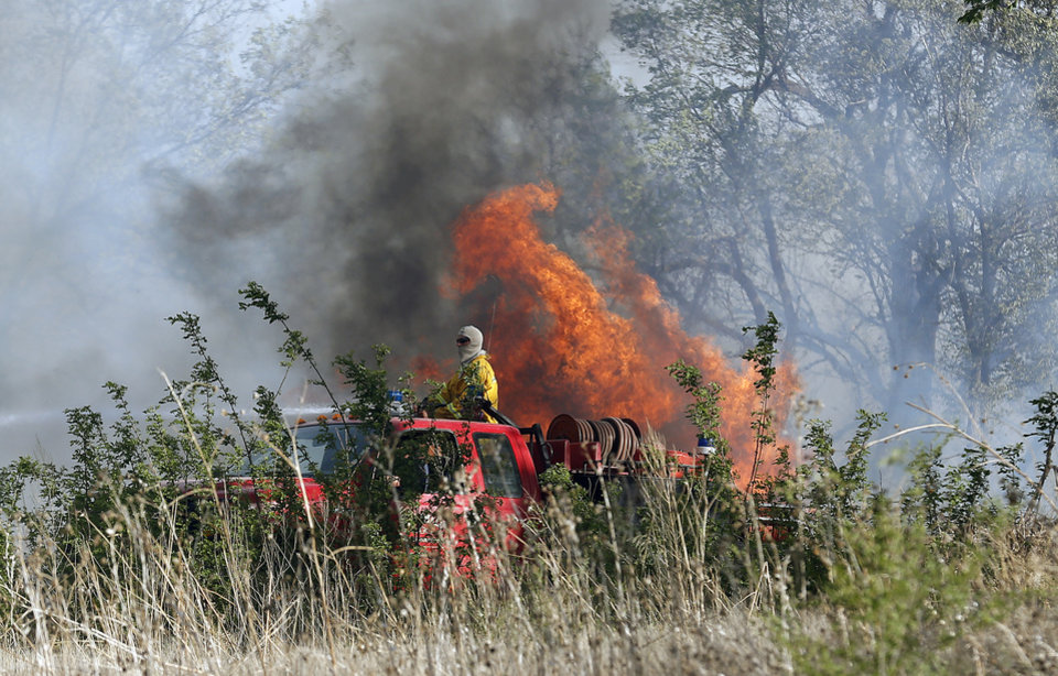 Photo - A firefighter puts out flames near East Seward Road and Oak Hill Road,  Sunday, May 4, 2014. Photo by Sarah Phipps, The Oklahoman