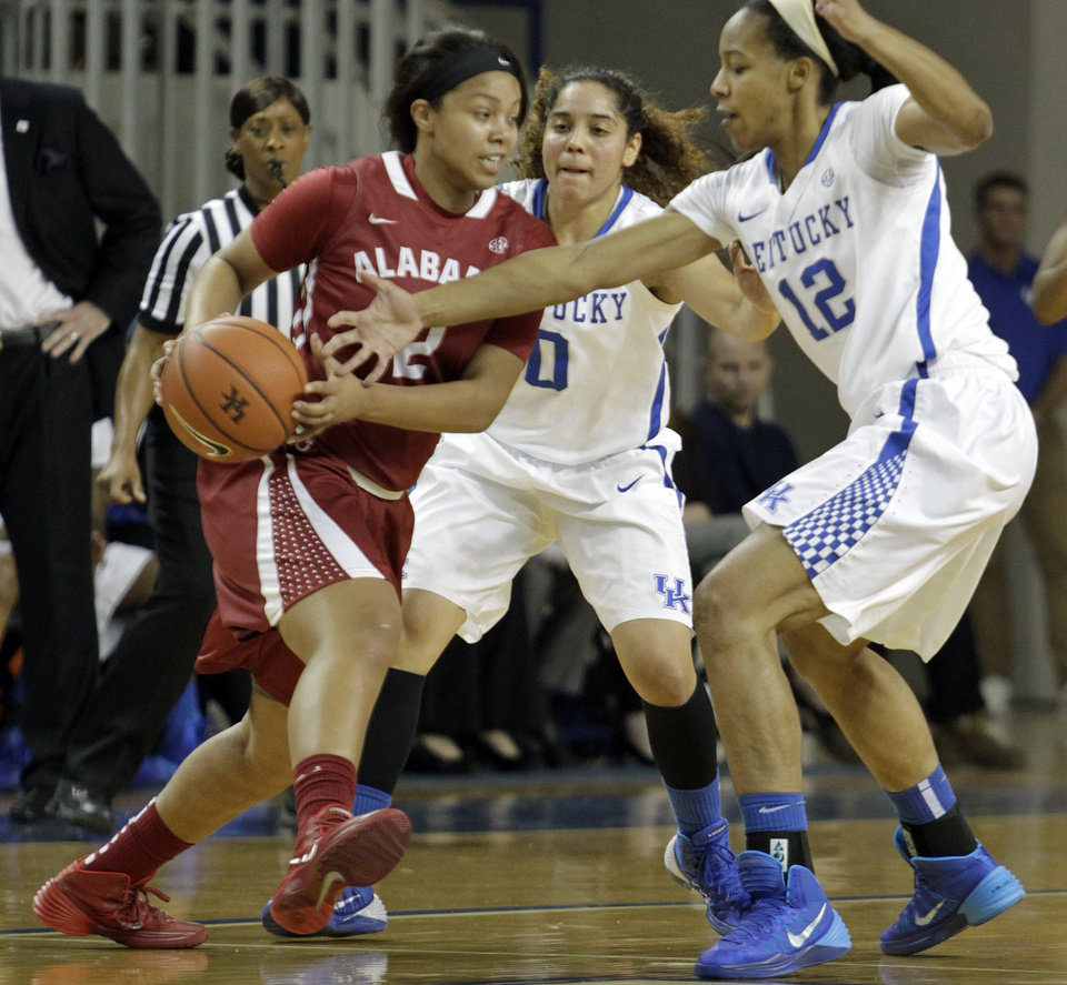 Photo - Alabama's Courtney Hunter, left, is pressured by Kentucky's Jelleah Sidney (12) and Jennifer O'Neill (0) during the first half of an NCAA college basketball game, Thursday, Jan. 23, 2014, in Lexington, Ky. (AP Photo/James Crisp)