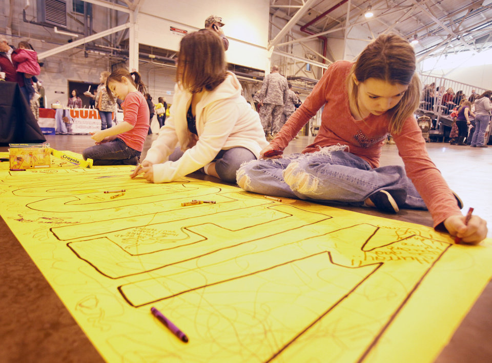 Kayla Livcy (left), Carmen Kissner and Gabby Kissner create a welcome sign, as soldiers from the 45th return from a year's deployment in Afghanistan to waiting family members in Oklahoma City, OK, Saturday, March 3, 2012. By Paul Hellstern, The Oklahoman