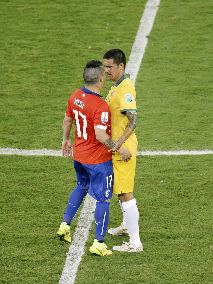 Photo - Australia's Tim Cahill, right, and Chile's Gary Medel confront each other during the group B World Cup soccer match between Chile and Australia in the Arena Pantanal in Cuiaba, Brazil, Friday, June 13, 2014. (AP Photo/Michael Sohn)