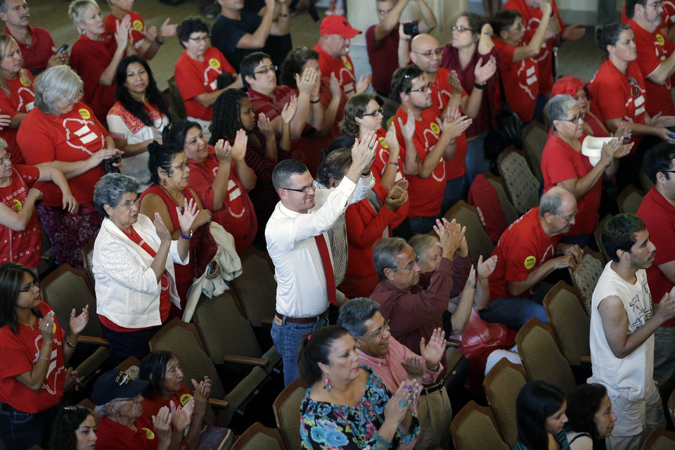 Photo - Supporters celebrate as the San Antonio city council votes on a non-discrimination ordinance, Thursday, Sept. 5, 2013, in San Antonio. The ordinance passed and in part will prohibit discrimination based on sexual orientation and gender identity. (AP Photo/Eric Gay)