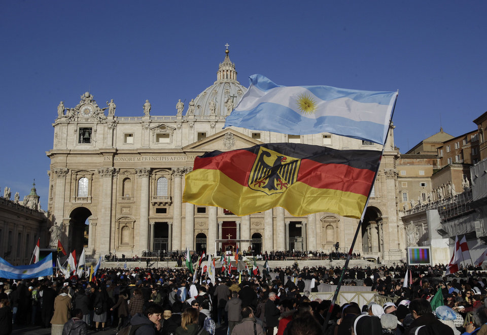 Visitiors wave flags from Germany and Argentina in Vatican square before the inauguration of Pope Francis in St. Peter's Square at the Vatican, Tuesday, March 19, 2013. (AP Photo/Michael Sohn)
