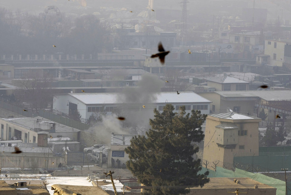 Photo - Dust rises from the site where a rocket fired by militants landed, as birds fly near the Kabul traffic police headquarters as it is attacked in Kabul, Afghanistan, Monday, Jan. 21, 2013. Taliban insurgents wearing suicide vests attacked the Kabul traffic police headquarters before dawn Monday, police said, and eyewitnesses heard numerous explosions while a gun battle was still raging nearly four hours later. (AP Photo/Musadeq Sadeq)