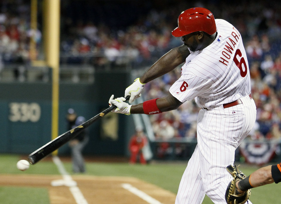 Photo - Philadelphia Phillies' Ryan Howard connects for an RBI-single to score Chase Utley during the third inning of a baseball game against the Miami Marlins, Saturday, April 12, 2014, in Philadelphia. (AP Photo/Tom Mihalek)