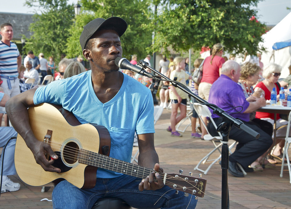 Photo - Steven Salewou entertains participants in this year's Taste of Edmond, part of LibertyFest celebrations. PHOTO BY M. TIM BLAKE, FOR THE OKLAHOMAN.  M. Tim Blake - FOR THE OKLAHOMAN