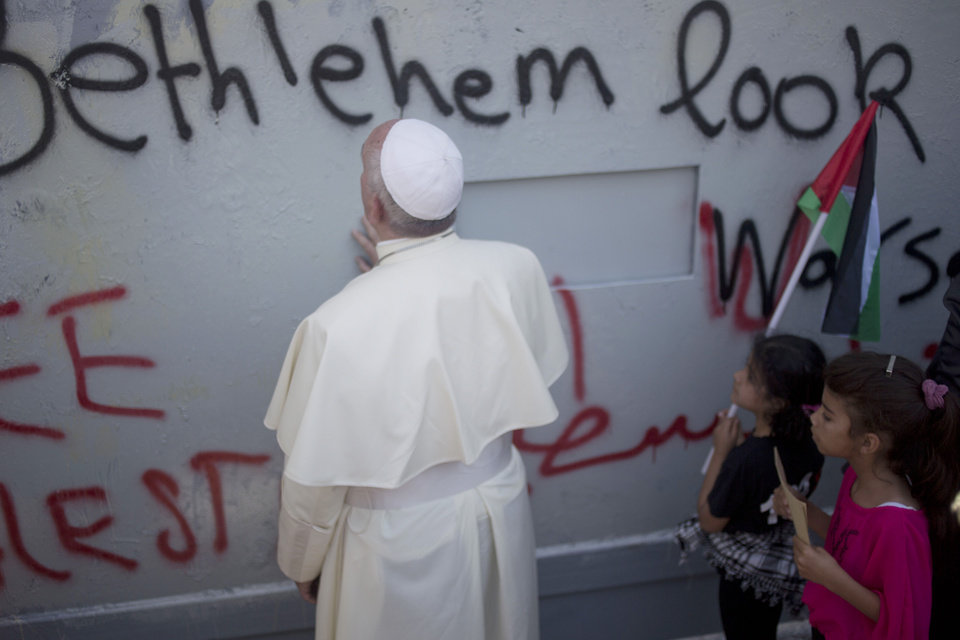 Photo - Pope Francis prays at Israel's separation barrier on his way to a mass in Manger Square next to the Church of the Nativity, traditionally believed to be the birthplace of Jesus Christ in the West Bank city of Bethlehem on Sunday, May 25, 2014. Francis called the Israeli-Palestinian stalemate