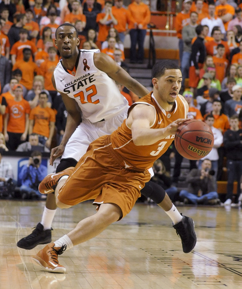 Oklahoma State guard Markel Brown (22) watches as Texas guard Javan Felix (3) drives toward the basket during the first half of an NCAA college basketball game in Stillwater, Okla., Saturday, March 2, 2013. (AP Photo/Brody Schmidt)