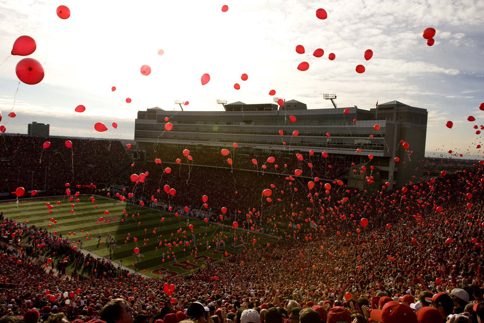 Photo - FANS / CROWD / OVERVIEW / COLORADO VS. UNIVERSITY OF NEBRASKA IN COLLEGE FOOTBALL AT MEMORIAL STADIUM, LINCOLN, NE - 11/28/2008 - Fans release balloons following Nebraska's first touchdown of the game against Colorado on Friday, November 28, 2008.   MICHAEL MCNAMARA/ For the Lincoln Journal Star  11/29/2008 pg 8D Husker Extra But the Huskers answered with a nine-play, 64-yard drive, when Joe Ganz found Nate Swift for a 2-yard touchdown. That set off the sea of red balloons (below). Colorado's Patrick Mahnke (bottom left) loses his helmet during a second-quarter hit on Nebraska's Niles Paul. Bo Pelini (bottom right) greets his first group of seniors before the game, including offensive lineman Matt Slauson. MICHAEL MCNAMARA/ For the Lincoln Journal Star ORG XMIT: 0911062217293032