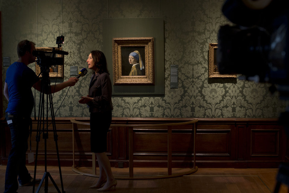 Photo - Director Emilie Gordenker is interviewed as she stands next to Johannes Vermeer's Girl with a Pearl Earring (approx. 1665) during a preview for the press of the renovated Mauritshuis in The Hague, Netherlands, Friday, June 20, 2014. The Mauritshuis will open its doors to the public for free from 8 pm till midnight on Friday June 27th after the official ceremonial opening. From June 28 onwards the museum will revert to regular opening hours. (AP Photo/Peter Dejong)