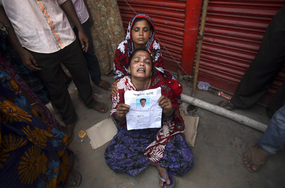 Photo - A woman grieves for her son who was trapped in the collapsed garment factory building and managed to survive for three days while being fed food and water passed to him by rescue workers but died later, Tuesday 30, April, 2013 in Savar, near Dhaka, Bangladesh. Emergency workers hauling large concrete slabs from the collapsed eight-story building said Tuesday they expect to find many dead bodies when they reach the ground floor. (AP Photo/Wong Maye-E)