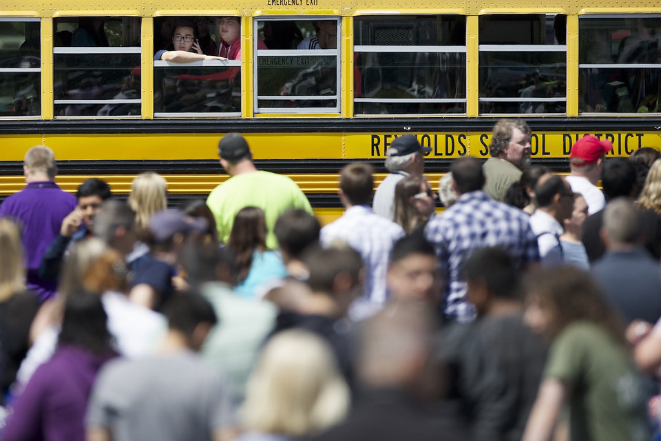 Photo - Students try to communicate and locate their family while waiting on a school bus as they arrived at a shopping center parking lot in Wood Village, Ore., after a shooting at Reynolds High School Tuesday, June 10, 2014, in nearby Troutdale. A gunman killed a student at the high school east of Portland Tuesday and the shooter is also dead, police said. . (AP Photo/Troy Wayrynen)