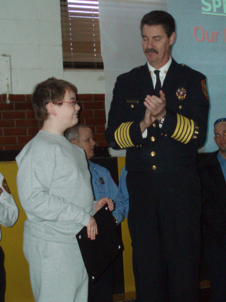 Fire Chief Randy Olsen presents Cory Burns with certificate of recognition<br/><b>Community Photo By:</b> Casey Hoeflein<br/><b>Submitted By:</b> Jerry,