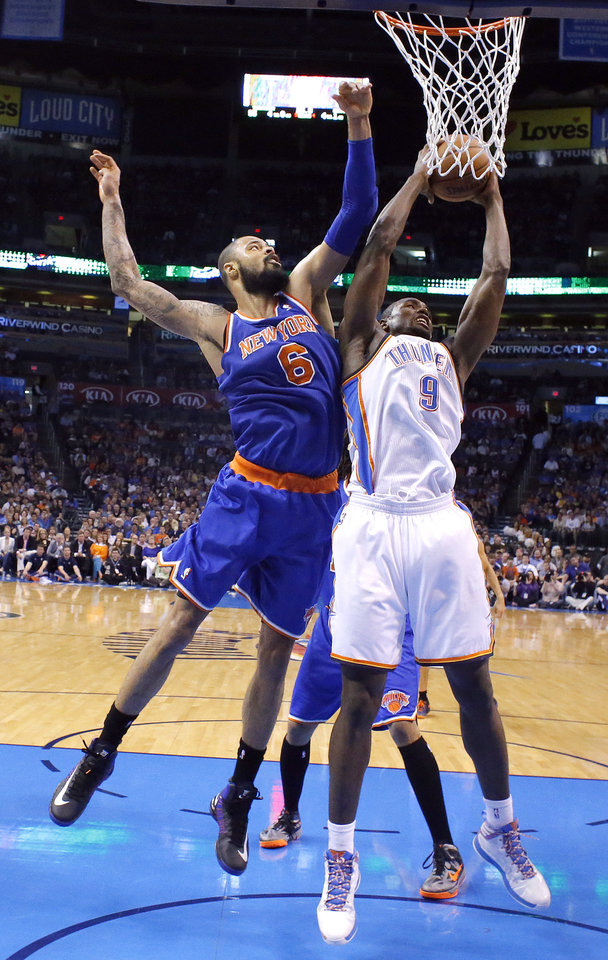 Photo - Oklahoma City's Serge Ibaka (9) grabs a rebound from New YorK's Tyson Chandler (6) during NBA basketball game between the Oklahoma City Thunder and the New York Knicks at the Chesapeake Energy Arena, Sunday, April 7, 2010, in Oklahoma City. Photo by Sarah Phipps, The Oklahoman