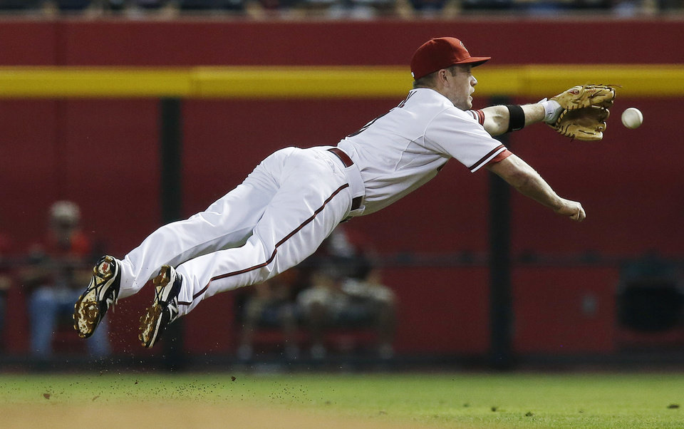 Photo - Arizona Diamondbacks' Aaron Hill dives but is unable to come up with a ball hit by Atlanta Braves' Jason Heyward during the first inning of a baseball game on Friday, June 6, 2014, in Phoenix. (AP Photo/Ross D. Franklin)