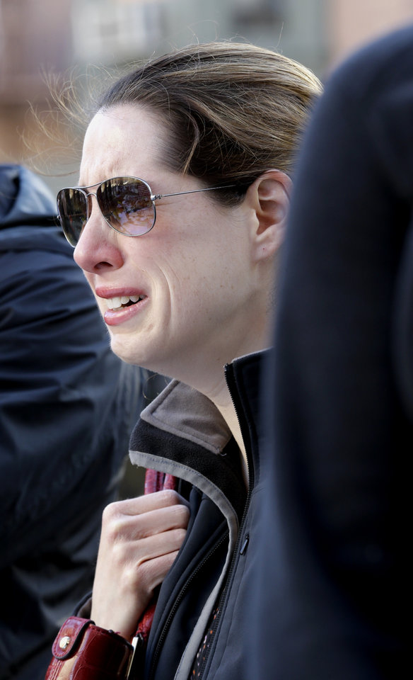 Photo - A woman cries at a makeshift memorial on Boylston Street in Boston, near the blast site of the Boston Marathon explosions, Thursday, April 18, 2013. The city continues to cope following Monday's explosions near the finish line of the marathon. (AP Photo/Julio Cortez)