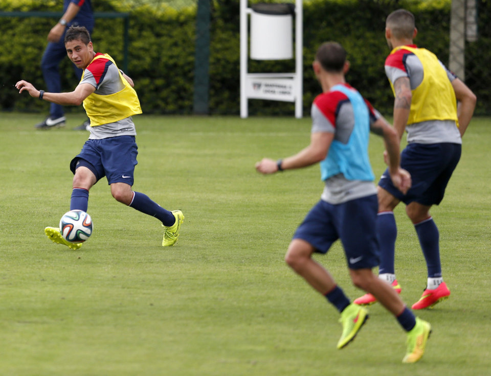 Photo - United States' Alejandro Bedoya, left, passes the ball in the direction of Brad Davis, center, and Clint Dempsey during a training session at the Sao Paulo FC training center in Sao Paulo, Brazil, Wednesday, June 11, 2014. The U.S. will play in group G of the 2014 soccer World Cup. (AP Photo/Julio Cortez)