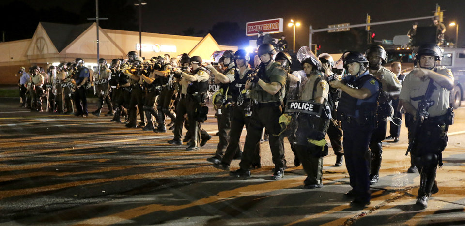 Photo - Police advance to clear people Monday, Aug. 18, 2014, during a protest for Michael Brown, who was killed by a police officer Aug. 9 in Ferguson, Mo. Brown's shooting has sparked more than a week of protests, riots and looting in the St. Louis suburb. (AP Photo/Charlie Riedel)