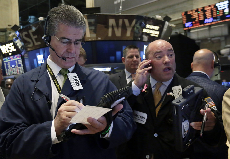 Photo - Traders Daniel Kryger, left, and Christopher Morie work on the floor of the New York Stock Exchange Wednesday, Aug. 6, 2014. Worries about Russian troops massing near the Ukrainian border are pushing stocks slightly lower. (AP Photo/Richard Drew)