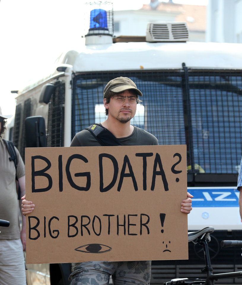 Photo - A protester stands in front of a police car during a demonstration agains supposed NSA surveillance in Germany, in Berlin, Germany Saturday July 27, 2013. (AP Photo/dpa, Wolfgang Kumm)