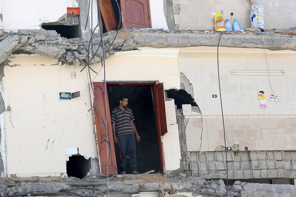 Photo - Palestinians inspect the rubble of a house after it was hit by an Israeli missile strike in Gaza City, Friday, July 11, 2014. Israel launched the Gaza offensive to stop incessant rocket fire that erupted after three Israeli teenagers were kidnapped and killed in the West Bank and a Palestinian teenager was abducted and burned to death in an apparent reprisal attack. The military says it has hit more than 1,100 targets already, mostly what it identified as rocket-launching sites, bombarding the territory on average every five minutes. (AP Photo/Hatem Moussa)