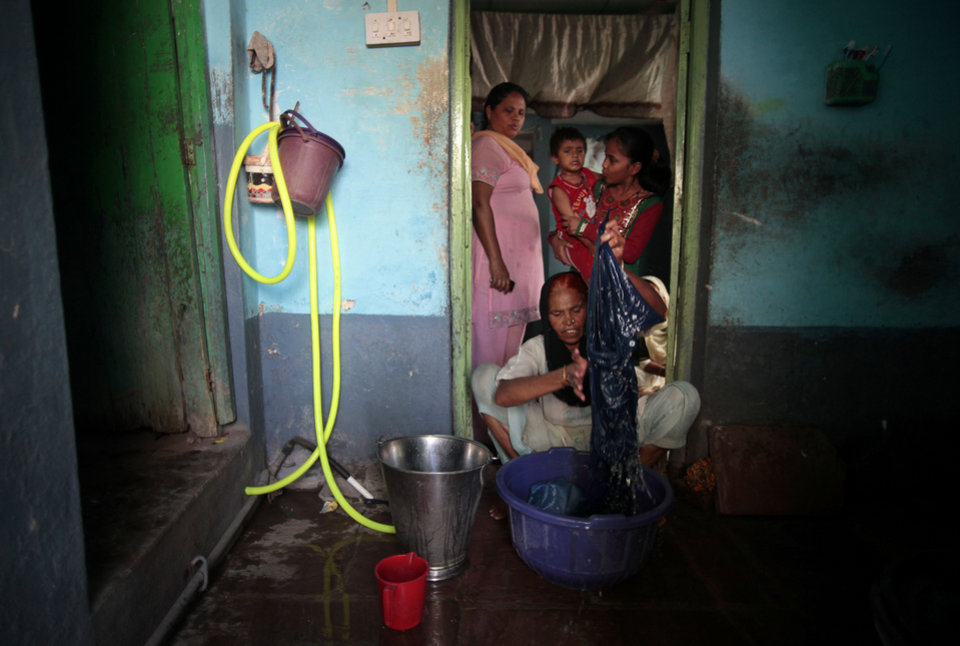 Photo -   In this May 10, 2012 photo, Fatima Munshi, working as domestic help, washes clothes at a house in Khandwa, India. Living in Australia, Saroo Brierley, 30, reunited with his biological mother, Munshi, in February 2012, 25 years after an ill-fated train ride left him an orphan on the streets of Calcutta. (AP Photo/Saurabh Das)