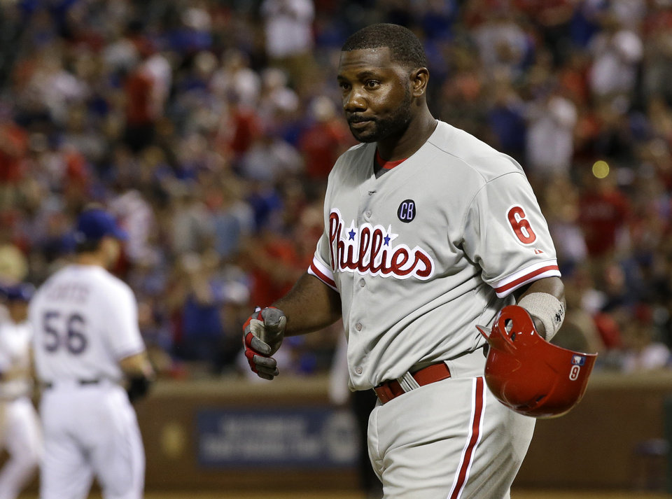 Photo - Philadelphia Phillies' Ryan Howard removes his batting helmet after being struck out by Texas Rangers' Neal Cotts (56), leaving two runners on in the eighth inning of a baseball game, Tuesday, April 1, 2014, in Arlington, Texas. The Rangers won 3-2. (AP Photo/Tony Gutierrez)
